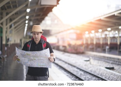 Handsome man wanderer traveler look searching direction on location map while traveling at train station, Happy male tourist searching road to hotel on map foreign city during vacation