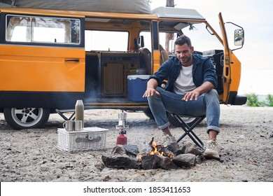 Handsome man warms his hands on the flame over the campfire. Picnic at the forest. Camping concept
