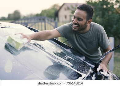 Handsome man washing car with sponge and foam
