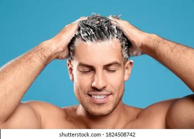 Handsome man washing hair on light blue background