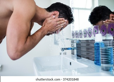 Handsome man washing his face in bathroom