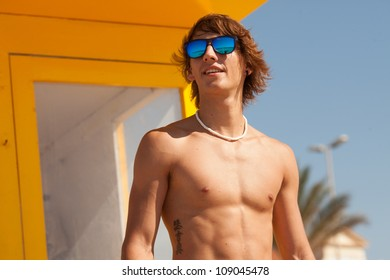 handsome man watching the sea on a lifeguard house