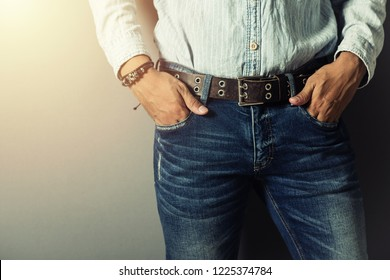 The handsome man wear blue jeans and genuine leather belt.