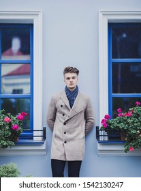 Handsome man wearing autumn clothes in street. Young guy with coat and scarf.