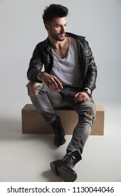 handsome man wearing black leather jacket looks to side while sitting on a wooden crate on light grey background, full length picture