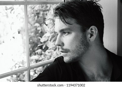 Handsome man wearing black shirt sitting in bay window looking out of glass