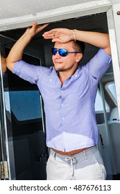 Handsome man wearing blue clothes posing in the boat.