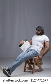 Handsome man wearing a casual outfit, sitting on a wooden chair, holding capper board and looking at it