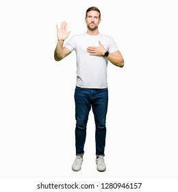 Handsome man wearing casual white t-shirt Swearing with hand on chest and open palm, making a loyalty promise oath