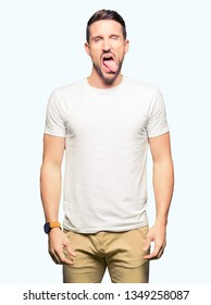 Handsome man wearing casual white t-shirt sticking tongue out happy with funny expression. Emotion concept.