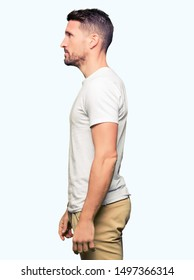 Handsome man wearing casual white t-shirt looking to side, relax profile pose with natural face with confident smile.