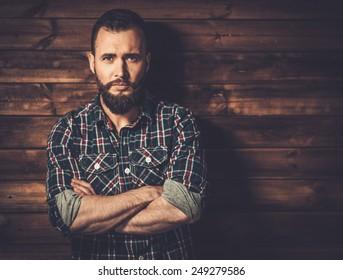 Handsome man wearing checkered  shirt in wooden rural house interior
