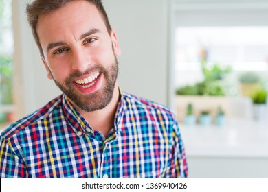 Handsome man wearing colorful shirt and smiling positive at the camera