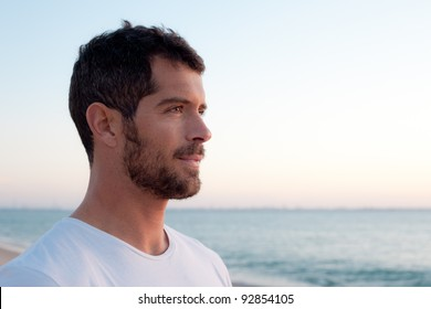Handsome man wearing comfortable white clothes looking at the ocean.
