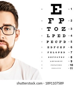 Handsome man wearing eyeglasses and eye chart for visual acuity test on white background