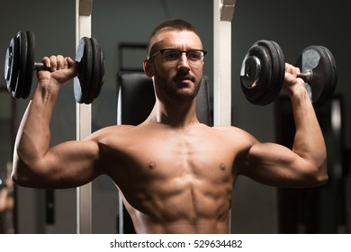 Handsome Man Wearing Eyeglasses Working Out Shoulders With Dumbbells In A Dark Gym