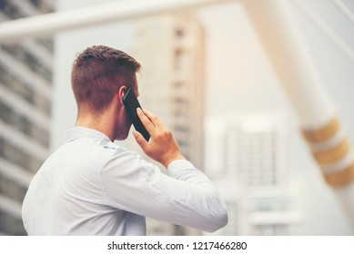 Handsome man wearing light blue shirt standing at the outdoor with the city background and talking on the mobile phone to connect the business, technology concept,selective focus,copy space.