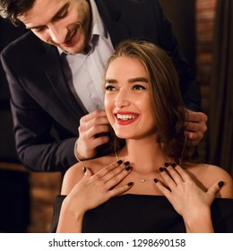 Handsome man wearing necklace on his attractive young woman. Present on Valentine's Day concept