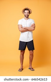 Handsome man wearing shorts and a t-shirt with folded hands posing against orange background