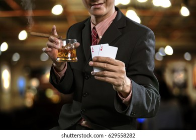A handsome man wearing a suit standing in club a has glass of whiskey and cigarette in right hand, and in left hand show winning in poker games, on casino club background