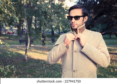 Handsome man wearing trench coat in park, vintage style