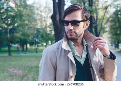 Handsome man wearing trench coat in park