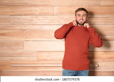Handsome man wearing warm sweater on wooden background. Space for text