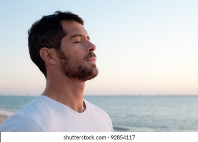 Handsome man wearing white deep breathing in front of the ocean.
