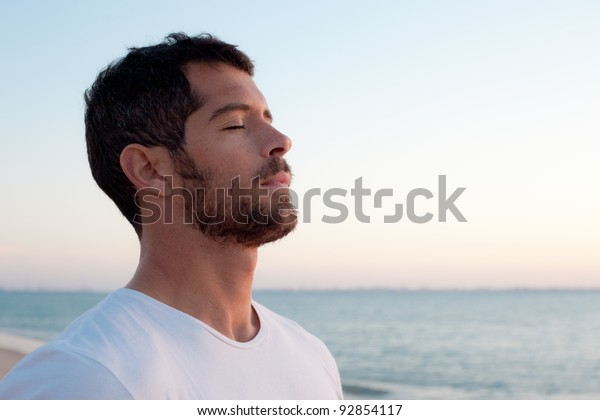 海の前で白い深呼吸をしているハンサムな男性。