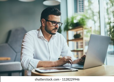 Handsome man wearing white shirt and eye glasses working with tablet in cafe, freelance concept, work from home job, freelancer job in progress, close up portrait.