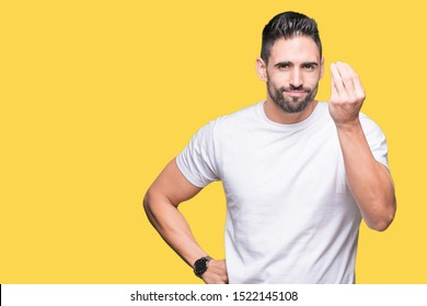 Handsome man wearing white t-shirt over yellow isolated background Doing Italian gesture with hand and fingers confident expression