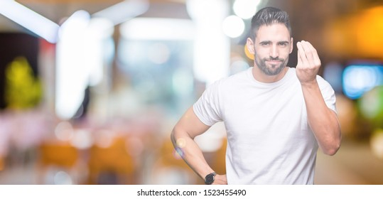 Handsome man wearing white t-shirt over night outdoors background Doing Italian gesture with hand and fingers confident expression