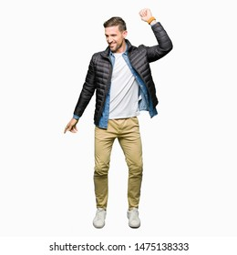 Handsome man wearing winter coat Dancing happy and cheerful, smiling moving casual and confident listening to music