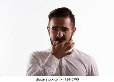 Handsome man whistling isolated on white background. Brunette hipster man in white shirt posing in studio. Emotions concept. Hardlight lightening concept.