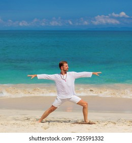 Handsome man in white clothes stand in yoga asana on sand beach. Yoga on the ocean in Bali.