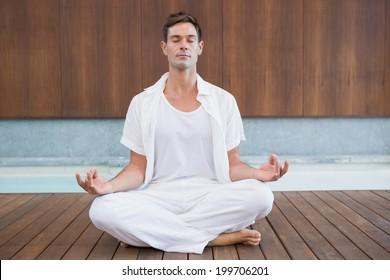 Handsome man in white meditating in lotus pose in health spa