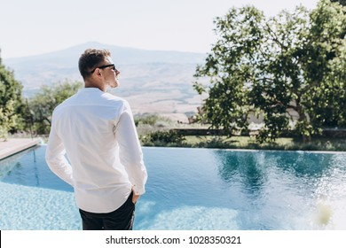 Handsome man in white shirt and black sunglasses poses beefore a waterpool