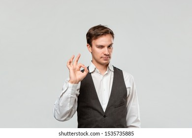 Handsome man in a white shirt and grey vest showing OK sign isolated over light grey background.