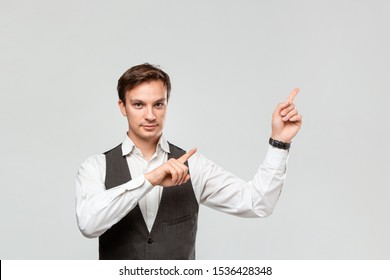 Handsome man in a white shirt and grey vest showing with his fingers at the empty space for advertising in the upper right corner of light grey background. Place for advertising
