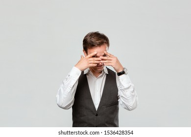 Handsome man in a white shirt and grey vest hiding behind his hands isolated over grey background. Concept of secret.