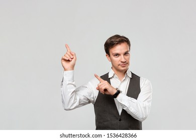 Handsome man in a white shirt and grey vest showing with his fingers at the empty space for advertising in the upper left corner of light grey background. Place for advertising