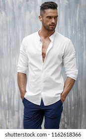 Handsome man in white shirt and shorts posing