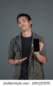 A handsome man who plays the phone in his hand and is on a gray background.