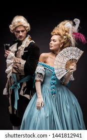 handsome man with wine glass near young victorian woman in wig holding fan on black