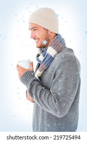 Handsome man in winter fashion holding mug against snow falling
