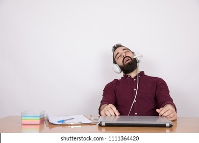 Handsome man working as a customer service, sitting on his desk, wearing the headset and he is looking very tired sleeping in the office.