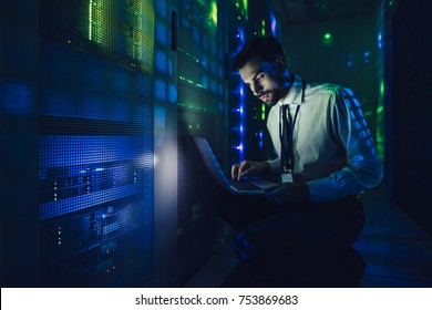 Handsome man is working in data centre with laptop.IT engineer specialist in network server room.Running diagnostics and maintenance.Technician examining server in big data center full of rack servers