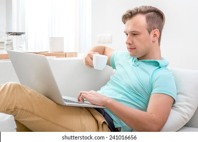 Handsome man working with laptop and drinking tea laying on the couch at home.