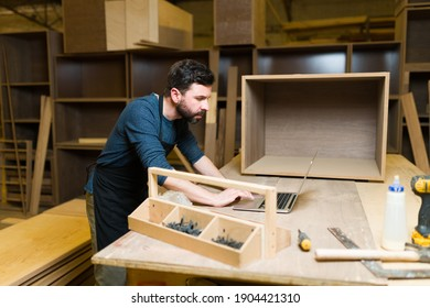 Handsome man working on the design of a new piece of furniture. Male worker typing on a laptop  in a woodshop