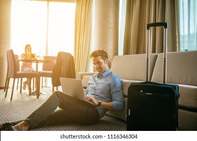 Handsome man working on his laptop in a hotel room.